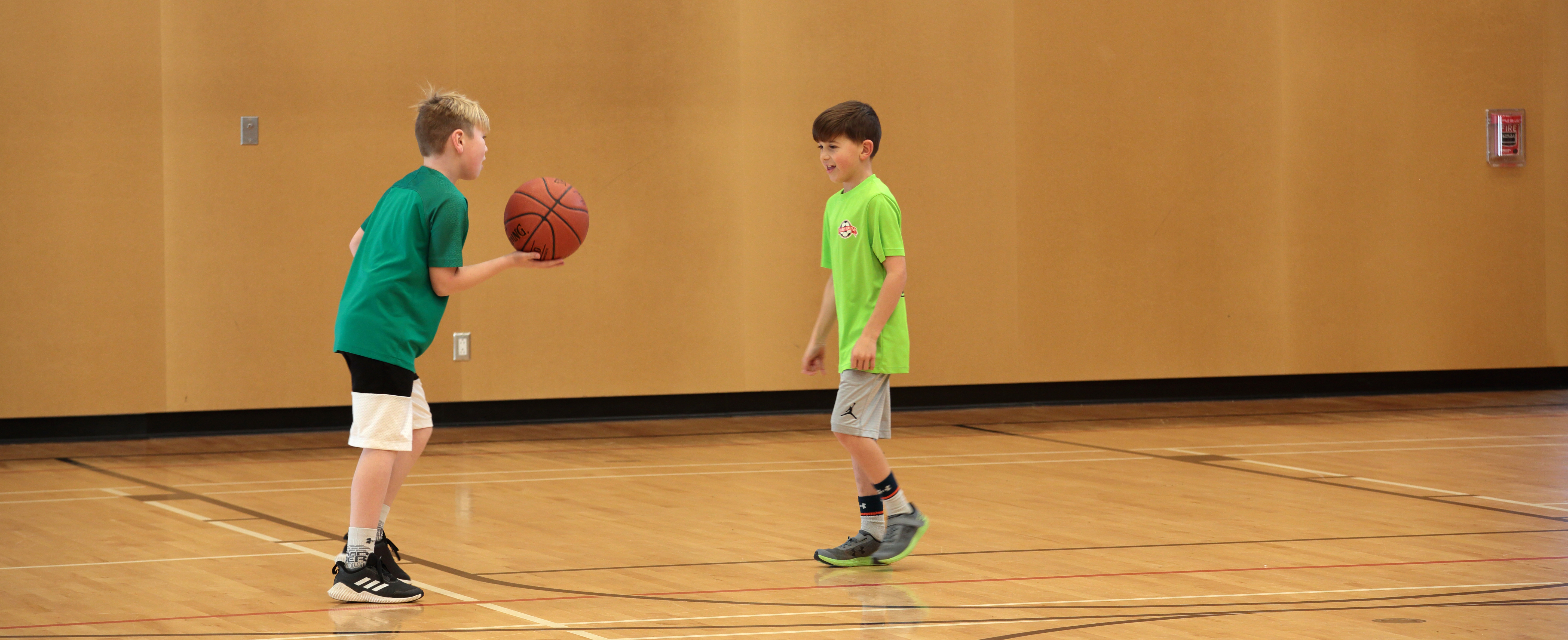 Two boys playing basketball in a gym