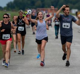 Runners celebrate with hands in the air as they participate in Jordan's Run The Runway.