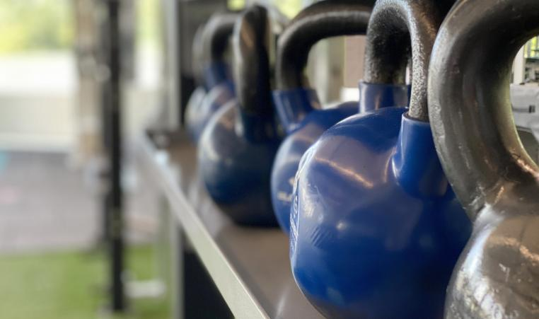 A row of blue and grey kettlebells sits in the turf fitness zone area of a YMCA.