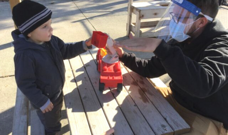 A young boy and Early Childhood Educator in PPE play at an outdoor picnic table with a red truck.