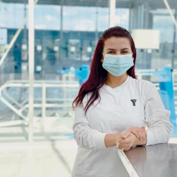 A young female staff member in a white shirt and mask smiles and poses at a health and fitness centre.